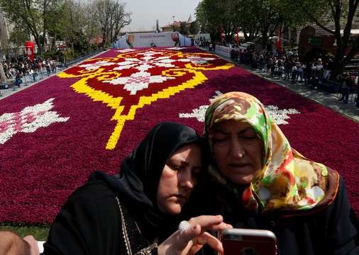 Women pose for a selfie with a huge carpet design formed by tulips at Sultanahmet square during the 13th Tulip Festival in Istanbul