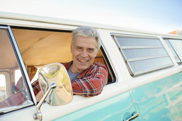 Senior man riding vintage camper van