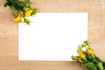 two bouquets of yellow roses and a white sheet of paper on a wooden table