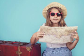 niña con maleta y mapa sobre fondo azul