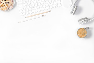 Beautiful light minimalistic mockup. White modern keyboard, mouse, headphones, pencils, vase with seashells and small cup of coffee on white background. Enjoying little things. Top view.