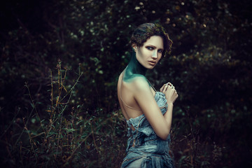 Beautiful model is posing in a forest as a nature spirit