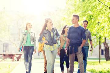 education, high school, communication and people concept - group of happy teenage students walking outoors