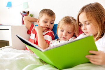 childhood, leisure and family concept - little kids reading book in bed at home