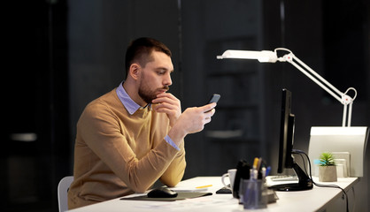 business, deadline and technology concept - man with smartphone and computer working at night office
