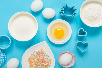 concept of the Easter bakery, various products for home baking, sugar, eggs and flour, coconut munt, top view, empty space for text on a blue background in the style of pop art mocap layout