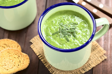 Fresh homemade cream of green pea and mint soup in enamel cups, garnished with stripes of mint leaves (Selective Focus, Focus in the middle of the mint leaves on the soup)