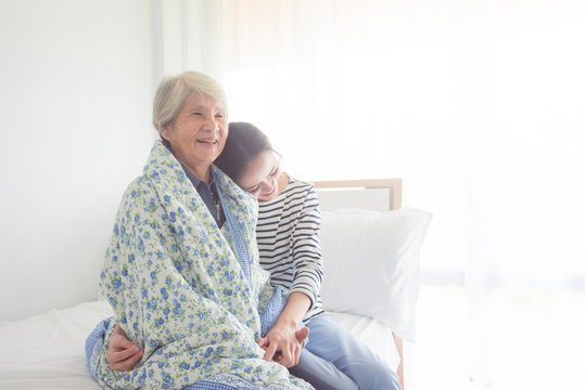 Asian daughter hugging her senior mother in bedroom at home