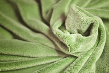 Green furry fleece fabric Blanket with a lot of folds relief