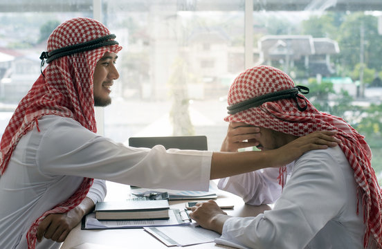 Arabian man comforting friend in office because receiving bad news and crying