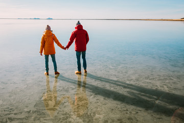 A young couple of travelers walk on ice. Iceland traveling