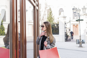 Young long hair girl with shopping bags on her hand looking at shop window