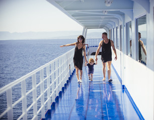 Happy family with cute son on summer vacation. Family travelling on cruise ship on sunny day. Family rest concept. Father, mother and child walk on deck of cruise liner with sea on background.