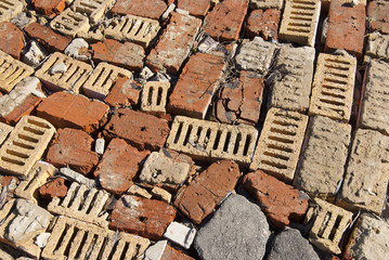 Homemade road from chaotically spread out bricks of different colors. Texture close-up
