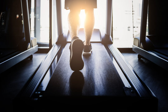 workout concept wite healthy people running on treadimill gym background