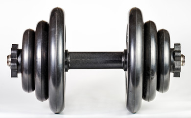 Black heavy dumbbell with rubberized discs and a rubberized handle for exercising in the gym