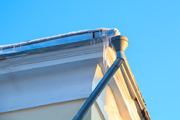 The drain pipe and icicles on the roof edge of the building in the spring.