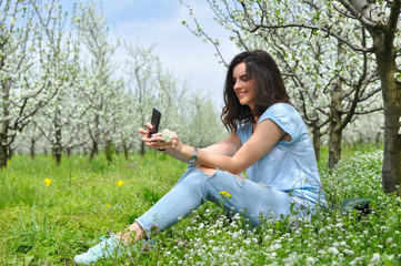 Girl texting on smartphone in a blooming orchid. Beautiful woman enjoy in nature in spring
