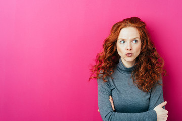 Young thoughtful woman against pink background