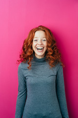 Laughing red haired woman standing in front of a pink background