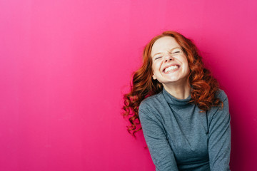 Young laughing woman against pink background