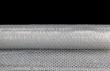 Roll of clear bubble wrap isolated on black background.