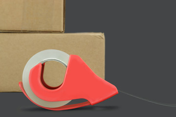 Roll of clear plastic packing tape with drop shadow. Brown cardboard box in blurred background. Isolated with copy space.