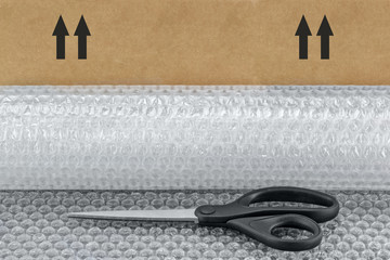 Scissors, roll of bubble wrap, and brown cardboard box background..