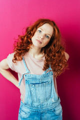 Young red-haired woman standing on pink background