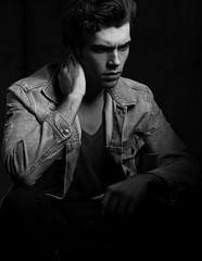 Thinking serious depression charismatic man looking down on dark shadow dramatic light background. Closeup portrait. Art. Black and white