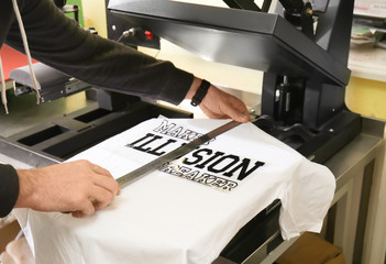 Young man printing on t-shirt at workshop