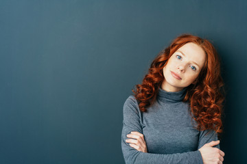Young cute red-haired woman on dark background
