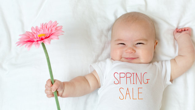 Spring Sale message with baby girl holding a flower