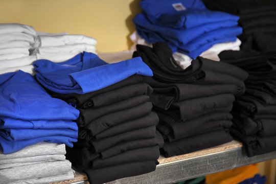 Stacks of t-shirts prepared for printing on shelf