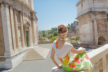 Pretty woman in floral dress on tourist viewpoint looking at view of Palatine Hill on Roman Forum ancient ruins with Arch of Septimius Severus and Santi Luca e Martina church outdoors