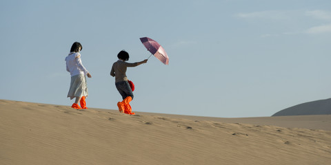 Girls walking on sand dune at Mingsha Shan, Dunhuang, Jiuquan, Gansu Province, China