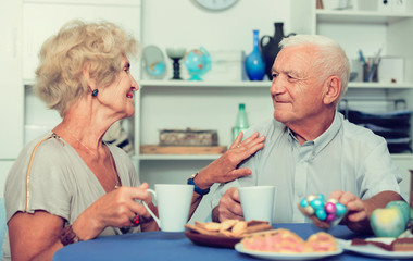 Smiling elderly spouses enjoying tea with sweets