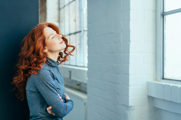 Young redhead woman standing daydreaming