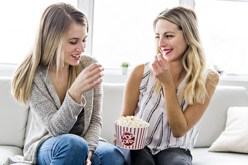 Two friends watching movie at home with popcorn