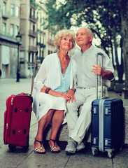 Portrait of senior couple of tourists resting on stone bench