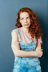 Worried pensive young redhead woman in dungarees