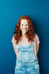 Happy cheerful young redhead woman in dungarees