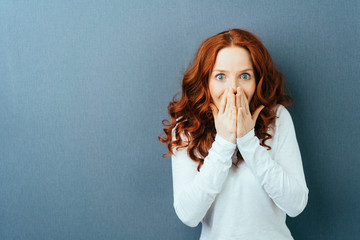 Excited young redhead woman staring at camera