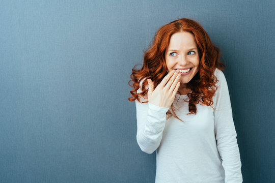 Cute young woman laughing behind her hand