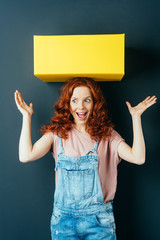 Young cheerful woman with yellow box on her head