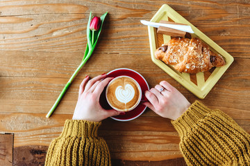 girl hold cup coffee and flower is on table