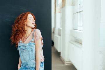 Lovely young redhead woman standing daydreaming