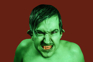 Young angry guy in the image of a goblin with green skin, grimaces. Isolated on red background.