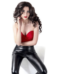 Fashion Sexy Woman Wearing Black Leather Pants and Red Top. Beautiful Young Model Girl with Long Curly Hair. Isolated on White.
