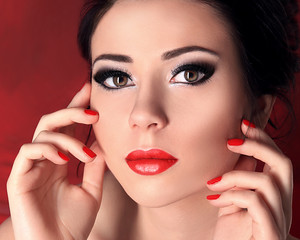 Beauty Fashion Model Girl Closeup Portrait over Red Background. Young Woman with Perfect Skin, Smoky Eyes Makeup, Long Eyelashes, Red Lips and Nails..
